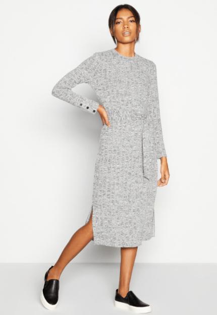 невысокая женщина в теплом платье